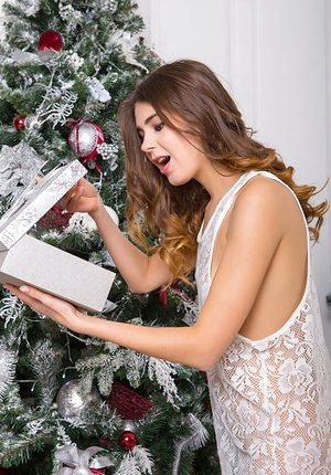 Brown-haired in white lace peels off by the Xmas tree to expose her torrid teenage figure