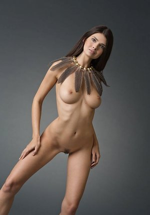 Erotic glamour model Jasmine A in feather necklace displaying thin nude bod