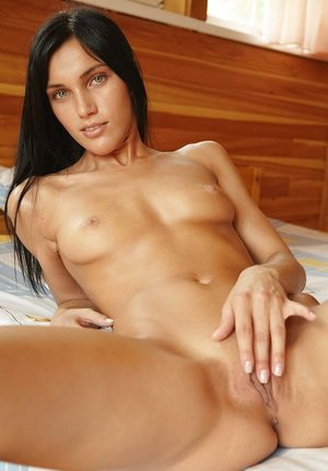 Teenage with a handsome slender body Megan E kneads her thirsty muff in the wooden house