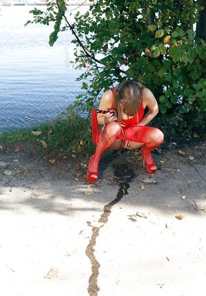 Pretty Natalie Russ in ponytails outside toying vulva in crimson sheer pantyhose