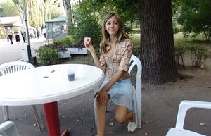 Youthfull light-haired fledgling gobbling ice juice posing non naked in public