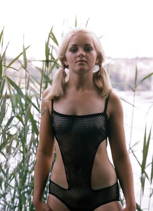 Blond with adorable ponytails posing in her fishnet underwear outdoors