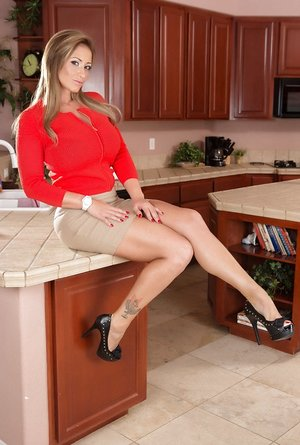White cougar Eva Notty works free of a miniskirt for naked poses in kitchen