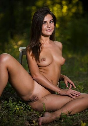 Youthfull looking brown-haired Arina B doffs lingerie for bare poses beside forest